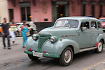 Havana, Cuba; a classic 1938 Chevy Master Deluxe car drives down the street in Havana
