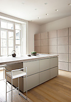 A contemporary, minimalist kitchen with a flush cupboard wall and a central island unit with breakfast bar.