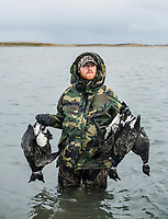 Guide Ben Teale with Four Flyways Outfitters collecting and hunting brant in Cold Bay, Alaska, Wednesday, November 2, 2016. The Izembek National Wildlife Refuge lies on the northwest coastal side of central Aleutians East Borough along the Bering Sea. Birds hunted include the long tailed duck, the Steller's Eider, the Harlequin, the King Eider and Brant.<br /> <br /> Photo by Matt Nager