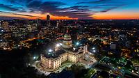 Imagen aerea de un vibrante naranjas y azules suavesen un cielo dramático que rodea el edificio del Capitolio del estado de Texas durante este espectacular atardecer en el centro de Austin, Texas.