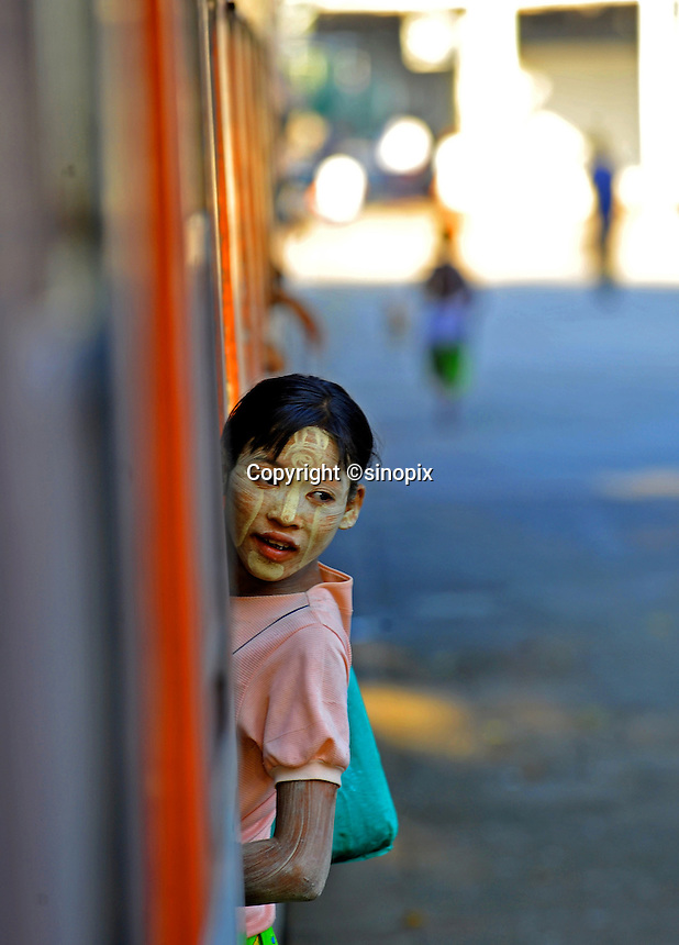 A young vendor with her face painted with rice paste to protect from the sun on the Mandalay to Rangoon train , Burma Nov 2008.  <br />