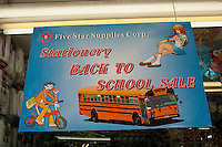 Back to school sales advertised in the window of a store in the primarily Dominican New York neighborhood of Washington Heights on Sunday, August 12, 2012. (© Richard B. Levine)