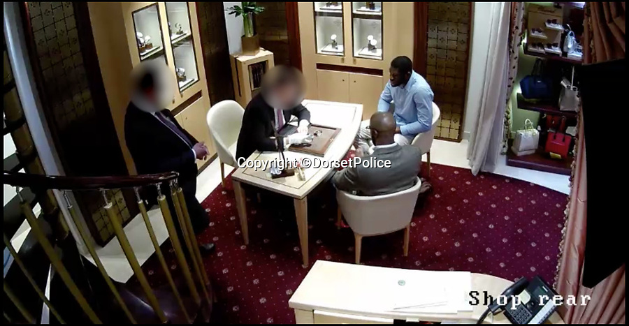 BNPS.co.uk (01202) 558833Pic: DorsetPolice/BNPS<br /> <br /> Screenshots from shocking CCTV footage of an armed robbery at a jewellers in Bournemouth.<br /> <br /> Mustafa Ali and Michael Adiat are trying on watches with shop assistant Ben-Simon Charles and shop owner Jeff Franses.<br /> <br /> Shocking CCTV that shows how two violent armed robbers posed as respectable customers before overpowering staff at a jewellers armed with handguns and a lump hammer has emerged.The two smart looking men sat down at a desk with shop assistant Ben-Simon Charles, who showed them luxury watches worth up to £50,000.Without warning one of them stands up, pulls out a pistol hidden under his jacket. His accomplice pulls a gun from his waistband and grabs Mr  Charles in a headlock while threatening to kill him and shop owner Jeff Franses.The assailant wielding the hammer threatens a third employee with it before smashing the reinforced glass of display cabinets to get to the expensive watches.