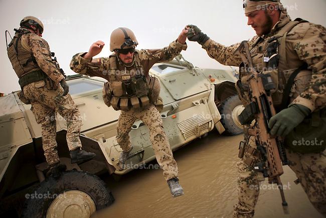 Afghanistan, 22.10.2011, Rahmat Bay. Anchdem in einer Furt ein Dingo fast im Fluss versunken ist, werden die Soldaten vom ECHO-Zug gerettet und das Fahrzeug geborgen. Die in Kundus stationierte 3. Task Force (ISAF) der Bundeswehr beginnt im Oktober 2011 die mehrtaegige Operation Orpheus. Durch Patrouillen in und um die Kleinstadt Nawabad (Dirstrikt Chahar Dareh) westlich von Kundus, Nordafghanistan, versuchen die rund 100 Infanteristen Rueckzugsorte Aufstaendischer unmoeglich zu machen. Unterstuetzt werden sie dabei durch einen Zug afghanischer Soldaten. An armored Dingo of the ECHO platoon sunk and stuck after the driver accidentially lost the way through a ford in the Konduz river near Rahmat Bay. After comrades supports the passengers to get out of the truck before they rescue it. In October 2011 Kunduz based 3.Task Force started a several days operation in and around Nawabad (District Chahar Dareh), west of Kunduz, northern Afghanistan. During the Operation Orpheus about 100 german infantry soldiers went out for patrols through the town and surrounding areas, which were expected as a retreat zone of insurgents. A platoon of afghan soldiers supports the german forces. © Timo Vogt/Est&Ost, NO MODEL RELEASE !! © Timo Vogt/Est&Ost, NO MODEL RELEASE !!