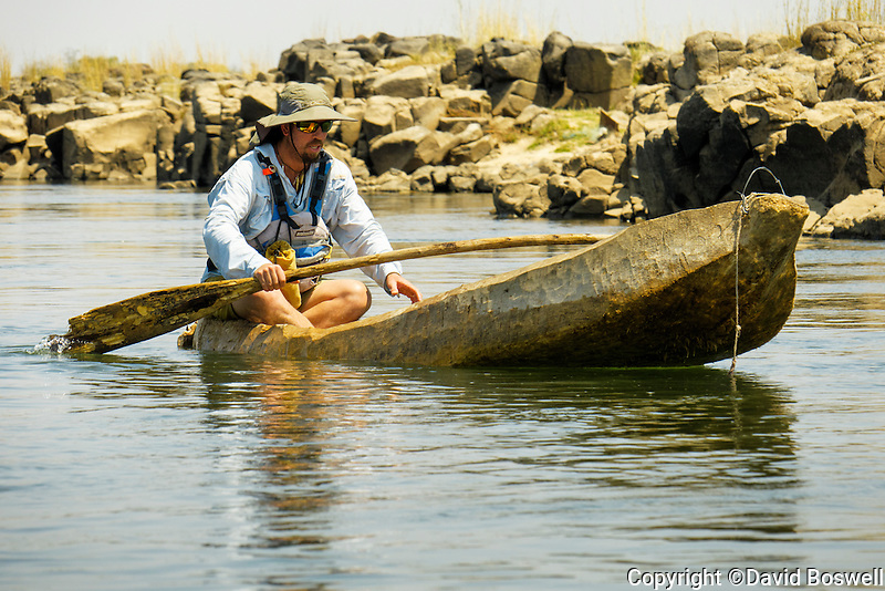 Bio Bio guide Diego Ibanez attempting to paddle a Mokoro, a dugout canoe used on the Zambezi River for transportation and fishing.