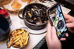 """BRUSSELS - BELGIUM - 16 December 2019 --  Restaurant """"Chez Léon"""" with a concept of serving """"Mussels and Fries"""", was established in 1893 in Brussels. It is the largest restaurant in the country in terms of turnover, number of customers and staff. -- A client taking a snap shot of the the served Mussels and Fries. -- PHOTO: Juha ROININEN / EUP-IMAGES"""