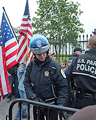 """A United States Park Police officer erects a barrier as members of the """"Million Veterans March on the Memorials"""" protest the closing of the memorials on the National Mall due to the partial shut-down of the government on Pennsylvania Avenue near the White House in Washington, D.C. on Sunday, October 13, 2013.<br /> Credit: Ron Sachs / CNP"""