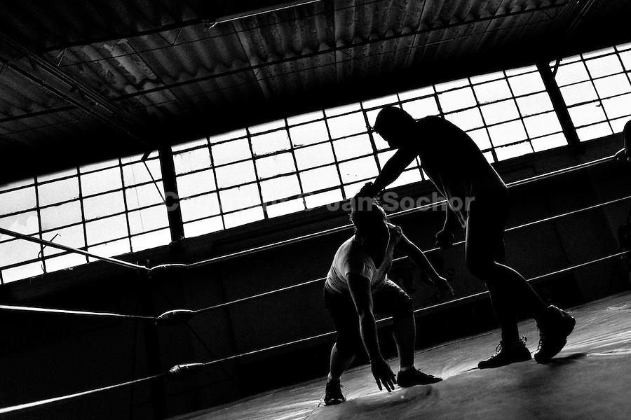 "A female Lucha libre wrestler trains with her male sparring partner at a combat sports gym in Mexico City, Mexico, 29 April 2011. Lucha libre, literally ""free fight"" in Spanish, is a unique Mexican sporting event and cultural phenomenon. Based on aerial acrobatics, rapid holds and the use of mysterious masks, Lucha libre features the wrestlers as fictional characters (Good vs. Evil). Women wrestlers, known as luchadoras, often wear bright shiny leotards, black pantyhose or other provocative costumes. Given the popularity of Lucha libre in Mexico, many wrestlers have reached the cult status, showing up in movies or TV shows. However, almost all female fighters are amateur part-time wrestlers or housewives. Passing through the dirty remote areas in the peripheries, listening to the obscene screams from the mainly male audience, these no-name luchadoras fight straight on the street and charge about 10 US dollars for a show. Still, most of the young luchadoras train hard and wrestle virtually anywhere dreaming to escape from the poverty and to become a star worshipped by the modern Mexican society."