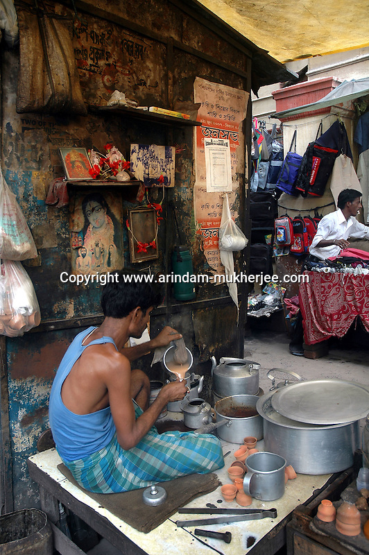 A man making tea at a street food stall at Dalhousie area in  Kolkata. Street food stalls are serving the office goers for decades. All kind of Indian foods are available on the street at an affordable price. They sale them openly. Street food stalls are another results of unempoloyment and over poppulation. They serve millions of people in India. Kolkata, West Bengal,  India  7/18/2007.  Arindam Mukherjee/Landov