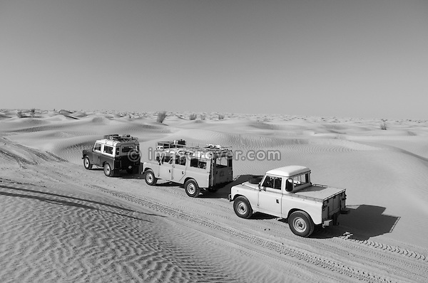 Africa, Tunisia, nr. Tembaine. Three historic Series Land Rovers crossing through a sandfield close to Tembaine on the eastern edge of the Grand Erg Oriental. --- No releases available, but releases may not be needed for certain uses. Automotive trademarks are the property of the trademark holder, authorization may be needed for some uses.  --- Info: Image belongs to a series of photographs taken on a journey to southern Tunisia in North Africa in October 2010. The trip was undertaken by 10 people driving 5 historic Series Land Rover vehicles from the 1960's and 1970's. Most of the journey's time was spent in the Sahara desert, especially in the area around Douz, Tembaine, Ksar Ghilane on the eastern edge of the Grand Erg Oriental.
