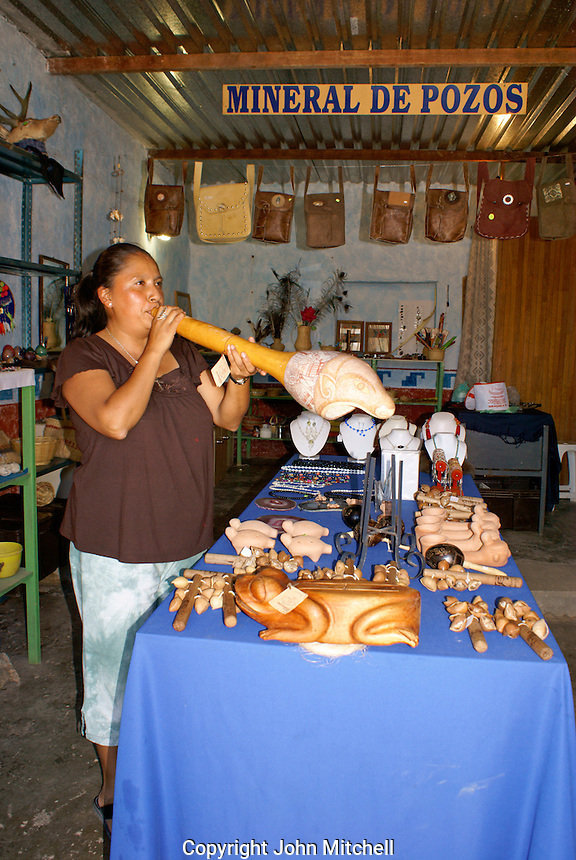 Griselda Gomez blowing into a pre-Hispanic trumpet in her handicrafts store in  the 19th century mining town of Mineral de Pozos, Guanajuato, Mexico.