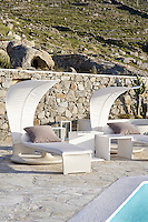 Modern sun loungers set beside a swimming pool on the terrace at the Villa Orpheus located on the Greek island of Mykonos.