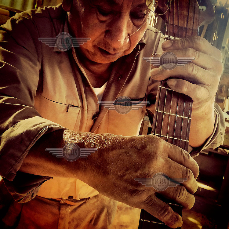Luceo Cabascango, 76, who has lived in the suburb of Rumihuaico since the early 1970's, holds a guitar he made out of an agave plant.
