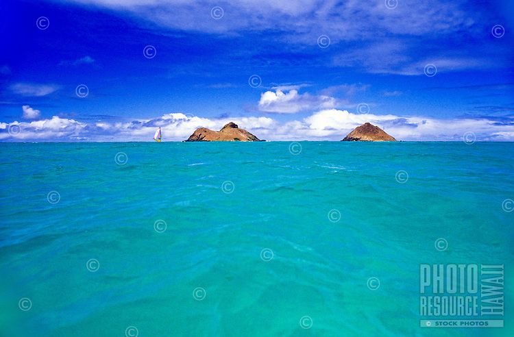 Turquoise water leading to the two Mokulua islands off Lanikai with wispy clouds on blue sky.