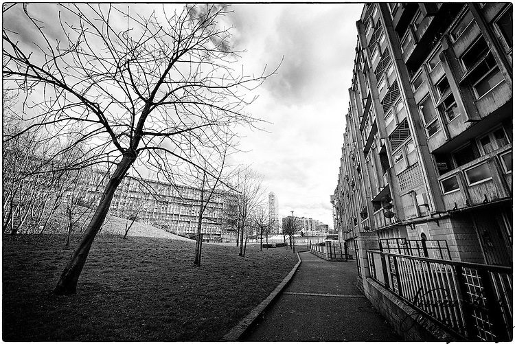 Robin Hood Gardens is a council housing complex in Poplar, London designed in the late 1960s by architects Alison and Peter Smithson and completed in 1972. It was intended as an example of the 'streets in the sky' concept: social housing characterised by broad aerial walkways in long concrete blocks, much like the Park Hill estate in Sheffield; it was both informed by, and a reaction against, Le Corbusier's Unit&eacute; d'Habitation.<br /> The estate is owned by Tower Hamlets Council. It covers about two hectares and consists of two long blocks, one of ten storeys, the other of seven, built from precast concrete slabs and containing 213 flats, surrounding a landscaped green area and a small hill made from construction spoil. The flats themselves are a mixture of single-storey apartments and two-storey maisonettes, with wide balconies (the 'streets') on every third floor. The complex is located near Blackwall DLR station. It is within sight of the nearby Balfron Tower; both are highly visible examples of Brutalist architecture.