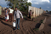 KHUTSONG, SOUTH AFRICA - OCTOBER 16: Bafana Mashata, age 17, fetches water with his mother Catherine on October 16, 2012, in Khutsong, South Africa. Khutsong, a black township. is located about 56 miles west of Johannesburg, and surrounded by gold mines. Because of recent strikes many mineworkers has been fired which is making the poverty worse here. His mother, Catherine Mashata, age 37, is unemployed. The communal toilets are dirty and often broken. (Photo by Per-Anders Pettersson)
