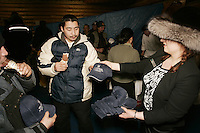 Brooke McGrath hands out ice cream bars and souvenir hats to Ruby residents during  the first musher to the Yukon River dinner sponsored by the Millenium hotel.  Paul Gebhart was the first to the Yukon.