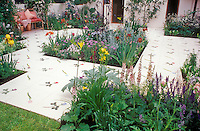 Wonderful painted patio rimmed & lush beds next to house, iris, patio furniture bench, lawn grass, backyard landscaping, inset flower beds in bloom with lots of color and variety and types. Garden & Deck Design: Sarah Brodie & Faith Dewhurst.