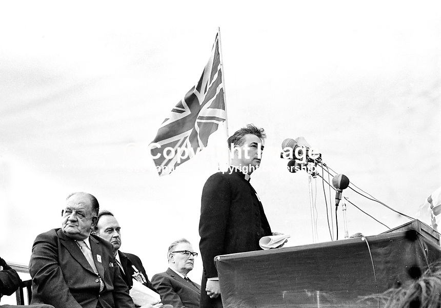 Rev Martin Smyth addressing an Ulster Vanguard Rally in Ormeau Park, Belfast. Also on the platform are from left: Billy Hull, leader of LAW (Loyalist Association of Workers, William Craig, prominent loyalist leader and one-time Ulster Unionist Minister of Home Affairs, and unknown man with glasses. NI Troubles. Union Jack.  Ref: 19720318001.<br />