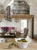 The open plan living/dining area has a mezzanine floor with industrial bookshelves built into the apex of the roof