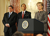 Washington, DC - January 22, 2009 -- United States President Barack Obama (C) looks on as his Secretary of State Hillary Clinton (R) speaks during an event where they announced the appointment of two new envoys to the Middle East, India and Pakistan, at the State Department  in Washington, DC, USA on 22 January 2009. Former Senator George Mitchell will serve as envoy to the Middle East and former Ambassador Richard Holbrook (L) will serve Pakistan and India..Credit: Matthew Cavanaugh - Pool via CNP