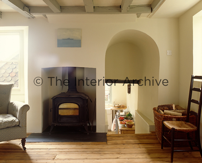 A large wood-burning stove is the focal point of the living room in this converted cakeshop in Sussex