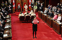 "Page Brigette DePape stands in the middle of the floor of the Senate as Governor General David Johnston delivers the Speech from the Throne in the Senate Chamber on Parliament Hill in Ottawa, Friday June 3, 2011. Moore has posted a giant photo on his website of 21-year-old Brigette DePape holding up a ""Stop Harper"" sign in the Senate chamber during Friday's throne speech. THE CANADIAN PRESS/Sean Kilpatrick"