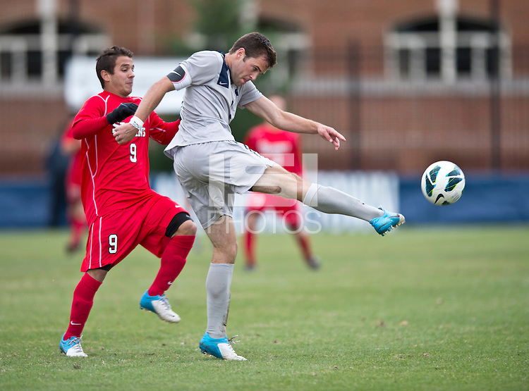 Tommy Muller (8) of Georgetown clears the ball away from Andres Vargas (9) of St. John's during the game at North Kehoe Field in Washington DC. Georgetown defeated St. John's, 2-1, in the Big East conference tournament quarterfinals.
