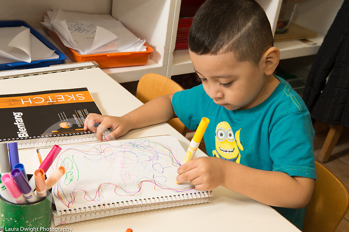 Education Preschool 4 year olds art activity boy drawing with markers and writing letters on his drawing