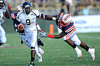 30 October 2010:  FIU running back Kedrick Rhodes (9) attempts to evade Florida Atlantic linebacker Randell Johnson (15) while carrying the ball in the first quarter as the Florida Atlantic University Owls defeated the FIU Golden Panthers, 21-9, at Lockhart Stadium in Fort Lauderdale, Florida.