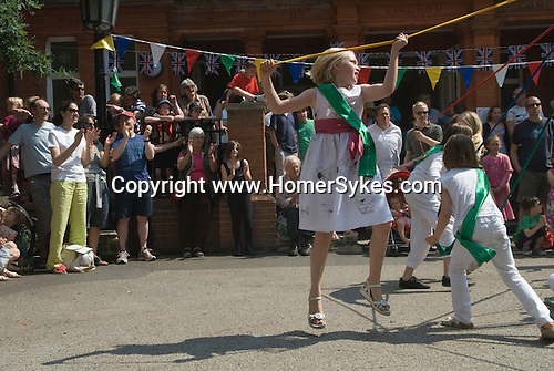 Children dancing around a May Pole Petersham village fete Richmond Surrey UK. Middle class white anglo saxon Britain.
