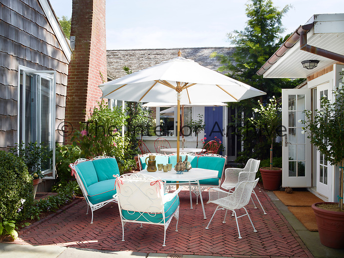White seating with blue cushions and a table with a parasol is arranged on the paved courtyard patio.