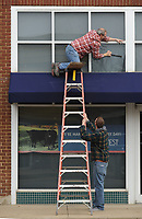 NWA Democrat-Gazette/ANDY SHUPE<br /> Roy Spencer (top) and Cody McCord, both glaziers with Fayetteville Glass Company, work together to fit new glass in a window Tuesday, March 14, 2017, above the doorway at the Arvest Bank location in downtown Prairie Grove. The duo replaced the glass after a crack formed in the former pane.