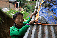 Kalpana Tamang (40), adjusts the tarpaulin sheet that was provided to her in the Home-in-a-Box which she now uses to cover the hole-riddled tin roof of her temporary shelter in Kavre, Bagmati, Nepal on 30 June 2015.  Kalpana, a widow with 3 children, has been supported by SOS Children's Villages for many years now and had receive the Home-in-a-Box after the earthquake destroyed her house, almost killing her two daughters. She now lives in a temporary shelter, sharing her dwelling with farm animals, and is trying to make ends meet by weaving bamboo baskets to supplement the financial assistance provided by SOS Childrens Villages. The NGO mostly supports her children's welfare and schooling as well as provides her with essential household and schooling items like kitchen utensils and school books and uniforms. Photo by Suzanne Lee for SOS Children's Villages