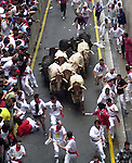 Participants run with fighting bulls during the San Fermin Festival´s running of the bulls, on July 13th, 2002 in Pamplona, Basque Country. On each day of the eight San Fermin festival days six bulls are released at 8:00 a.m. (0600 GMT) to run from their corral through the narrow, cobbled streets of the old navarre town over an 850-meter (yard) course. Ahead of them are the runners, who try to stay close to the bulls without falling over or being gored. (Ander Gillenea / Bostok Photo)
