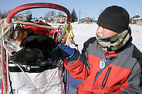 """Tuesday March 6, 2007   Nikolai resident Greg Tony pets """"Burt"""" one of Ramy Brooks' dogs  as it sits in the sled bag at the Nikolai checkpoint on Tuesday.  Burt was injured on the run from Rohn forcing Ramy to haul him the rest of the way and then drop him at Nikolai."""
