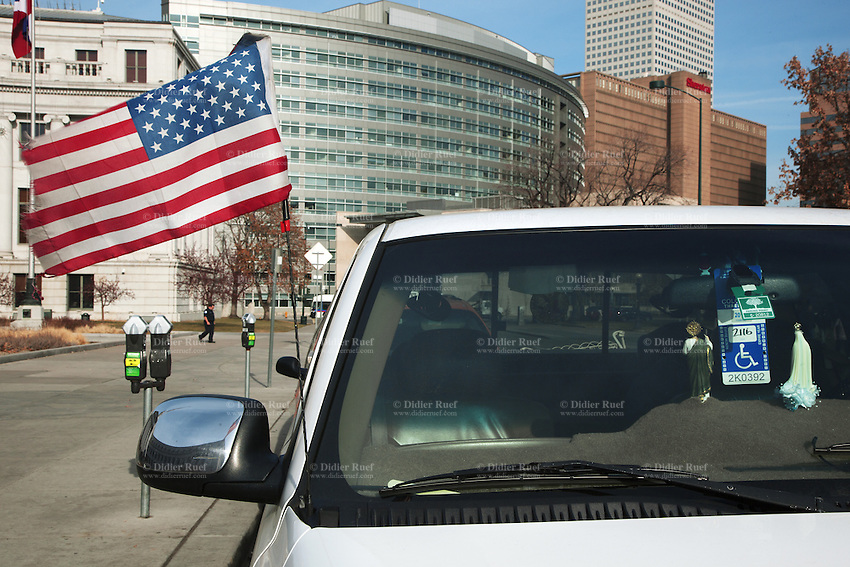 "USA. Colorado state. Denver. Downtown. A disabled sticker and two religious figurines on a pickup truck's dashboard. An american flag is blowing in the air. The national flag of the United States of America, often referred to as the American flag, consists of thirteen equal horizontal stripes of red (top and bottom) alternating with white, with a blue rectangle in the canton (referred to specifically as the ""union"") bearing fifty small, white, five-pointed stars arranged in nine offset horizontal rows of six stars (top and bottom) alternating with rows of five stars. 18.12.2014 © 2014 Didier Ruef"