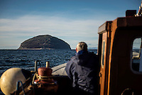 Mark McCrindle, skipper of the lobster boat M.V. Glorious looks out from its bows towards Ailsa Craig an unihabited volcanic island that is the source of the granite used to make most of the world's curling stones, including those used every four years in the Winter Olympics. The island is for sale with an asking price of GBP 1.6 million.