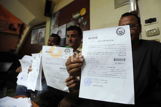 Supporters of Egyptian presidential hopeful, leftist, Hamdeen Sabahi, hold their authorization signatures for the nomination process at a registration office, in Beni Suef southern Cairo, April 11, 2014. Sabahi, who took third place in 2012 presidential elections, has said he would run against the country's powerful former military chief Abdel-Fattah el-Sissi, who led the overthrow of Islamist President Mohammed Morsi last summer, and who is widely expected to win in the late May election. Photo by Mohammed Bendari