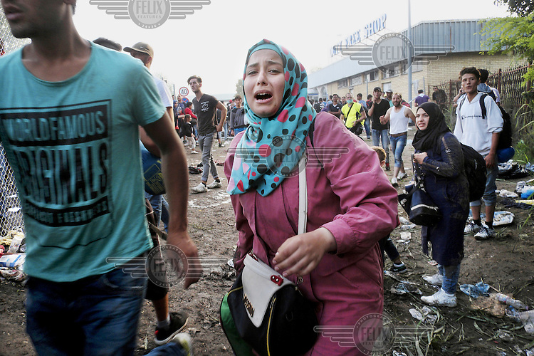Syrian woman cries as Hungarian riot police fires tear gas and water cannon at people trying to cross the border from Serbia. The newly completed razor wire fence that, as of 15 September 2015, sealed the border with Serbia leaving thousands of migrants and refugees stranded outside the European Union.