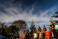 Colorful and enthusiastic Taiko Drummers perform under a cloud painted sky at the Fifth Annual San Leandro Moon Festival.
