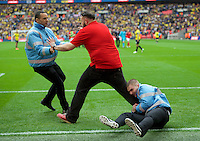 A Barnsley fans is wrestled to the ground at the end of the Johnstone's Paint Trophy Final match between Oxford United and Barnsley at Wembley Stadium, London, England on 3 April 2016. Photo by Alan  Stanford / PRiME Media Images.