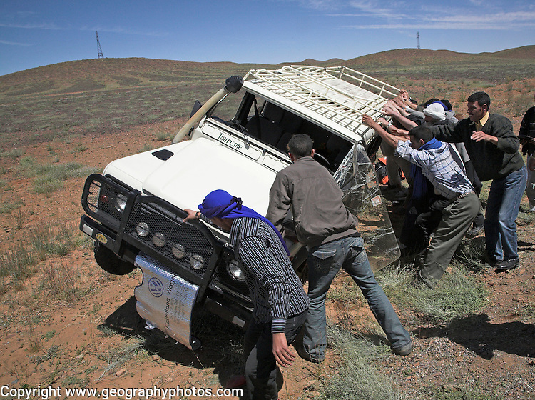 Following an accident a group of men roll a four wheel drive vehicle back onto its wheels in a desert area of Morocco, north Africa.