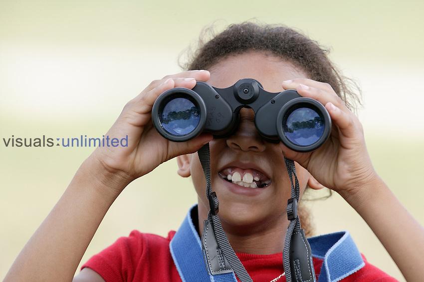 Young girl bird watcher with binoculars.