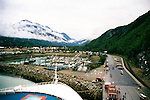 Docked At Skagway Port, Alaska, With Graffiti Hill On The Right And The Red Station For The White Pass And Yukon Railroad