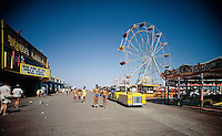 Wildwood Boardwalk & Aqua Circus in Wildwood, NJ. Tram Cars, Ferris Wheel & kids in bathing suits walking on the boardwalk.
