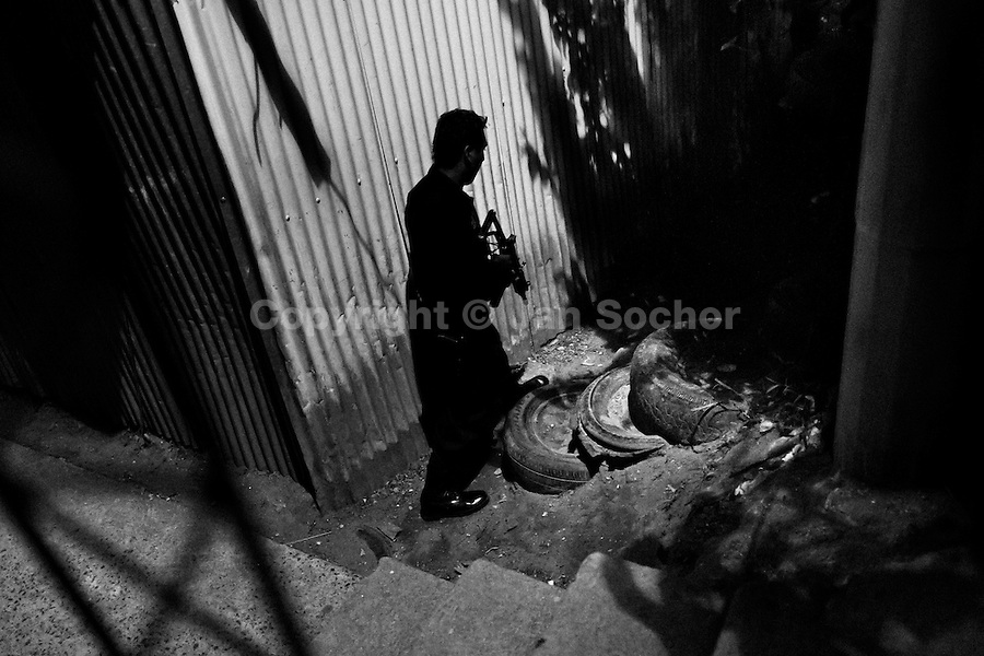 A policeman from the special emergency unit (Halcones) chases supposed gang members during the night in a gang neighbourhood of San Salvador, El Salvador, 15 December 2013. During the last two decades, Central America has become the deadliest region in the world that is not at war. According to the UN statistics, more people per capita were killed in El Salvador than in Iraq, in recent years. Due to the criminal activities of Mara Salvatrucha (MS-13) and 18th Street Gang (M-18), the two major street gangs in El Salvador, the country has fallen into the spiral of fear, violence and death. Thousands of Mara gang members, both on the streets or in the overcrowded prisons, organize and run extortions, distribution of drugs and kidnappings. Tattooed armed young men, mainly from the poorest neighborhoods, fight unmerciful turf battles with their coevals from the rival gang, balancing between life and death every day. Twenty years after the devastating civil war, a social war has paralyzed the nation of El Salvador.