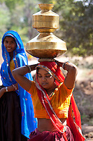 Indian woman carrying water pots on her head at Sawai Madhopur in Rajasthan, Northern India
