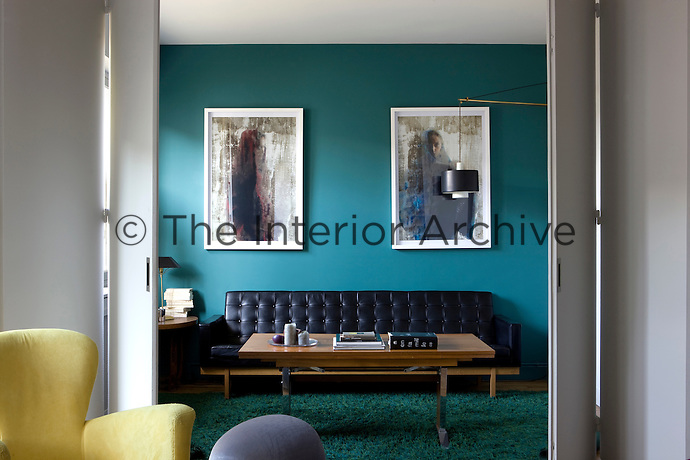 Sliding partitions have been designed to divide the small salon, painted a deep 50s petrol blue, from the main living room