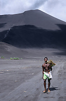 Man carrying kava roots on his shoulder in front of the Mount Yasur volcano, Tanna, Vanuatu.